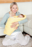 Mother holding her baby that is wrapped into a cover Stock Photo