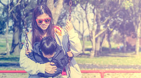 Mother Holding her child on a Swing playground with copy space Royalty Free Stock Photos
