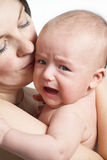 Mother Holding Her Crying Baby Stock Photos
