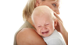 Mother holding her crying baby isolated Stock Images