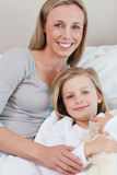 Mother holding her daughter on the bed Stock Image