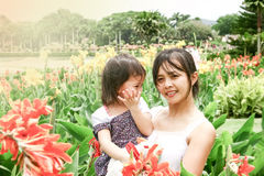 Mother holding her daughter in garden Royalty Free Stock Photo