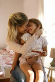 Mother holding her daughter in lap. Royalty Free Stock Photos