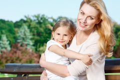 Mother holding her daughter in park Stock Photos