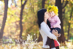 Mother holding her daughter in a wreath of maple Stock Image