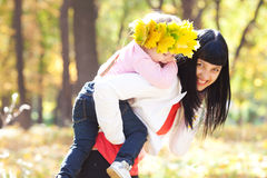 Mother holding her daughter in a wreath of maple Royalty Free Stock Image
