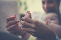 Mother holding in her hands baby feet. stock photos