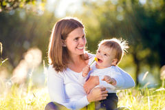 Mother holding her little son, sitting on the grass Royalty Free Stock Photos