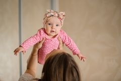 Mother holding her little daughter in the pink romper up in the Royalty Free Stock Photos