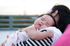 Mother holding her newborn baby in sexy dress while her was sleeping. Baby is sleeping on her mother shoulder at the rooftop. Royalty Free Stock Image