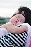 Mother holding her newborn baby in sexy dress while her was sleeping. Baby is sleeping on her mother shoulder at the rooftop. Stock Photo