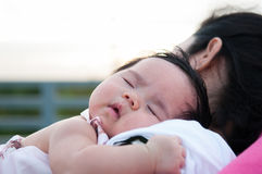 Mother holding her newborn baby in sexy dress while her was sleeping. Baby is sleeping on her mother shoulder at the rooftop. Royalty Free Stock Photo