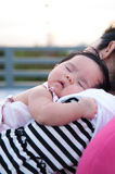 Mother holding her newborn baby in sexy dress while her was sleeping. Baby is sleeping on her mother shoulder at the rooftop. Stock Photos