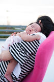 Mother holding her newborn baby in sexy dress while her was sleeping. Baby is sleeping on her mother shoulder at the rooftop. Royalty Free Stock Images