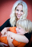 Mother holding her preschool son. Beautiful blond mother holding her preschool son against orange background Stock Photo