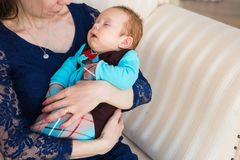 Mother holding her sleeping baby son in the room. Young mother holding baby son in the room Royalty Free Stock Images