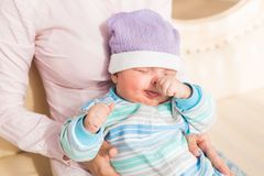 Mother holding her sleeping baby son in the room. Young mother infant baby son in the room Stock Images
