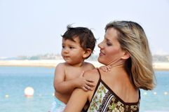 Mother holding her son on hands at beach Stock Photography