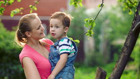 Mother holding her son and they talking outdoor Royalty Free Stock Photography