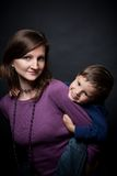 Mother holding his son a piggyback ride. Studio shot of mother holding his son a piggyback ride Stock Photo
