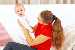 Mother holding intersted baby in hands Royalty Free Stock Images