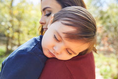 Mother holding kid boy sleeping in her shoulder Royalty Free Stock Photography