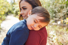 Mother holding kid boy sleeping in her shoulder Royalty Free Stock Images