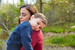 Mother holding kid boy tired in her shoulder Royalty Free Stock Photos