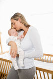 Mother holding and kissing her baby boy. At home Royalty Free Stock Photo