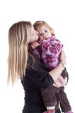 Mother holding and kissing little girl Stock Photography
