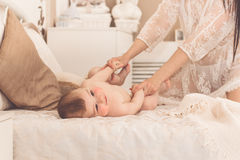 Mother is holding little baby boy by hands Royalty Free Stock Image