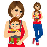 Mother holding little boy with baby carrier Royalty Free Stock Photography