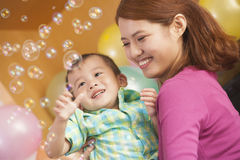 Mother Holding Little Boy While He Plays with Bubbles Royalty Free Stock Images