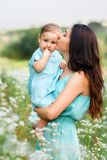 Mother holding little daughter on summer meadow Stock Photo