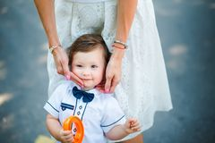 Mother holding little son on the cheek. Portrait of beautiful curly boy with a toy in his hands. Mom wipes cheek child Royalty Free Stock Photography