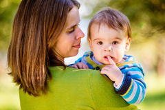 Mother holding little son in her arms, sunny nature Stock Images