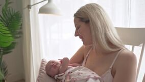 Mother holding newborn baby in chair