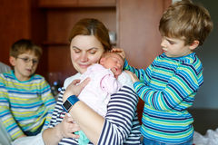 Mother holding newborn baby girl on arm with two kids boys Royalty Free Stock Photography