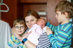 Mother holding newborn baby girl on arm with two kids boys Stock Photo