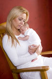 Mother holding newborn baby in rocking chair Stock Photography