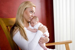 Mother holding newborn baby in rocking chair Royalty Free Stock Photography