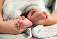 Mother holding newborn's feet Stock Images