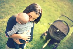 Mother holding newborn son in hands. Loving mother hand holding cute sleeping newborn baby child in park at sunset Stock Photos