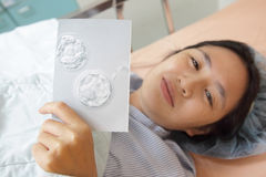 Mother holding a picture of twins fertilized egg Stock Photos
