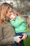 Mother holding shy smiling girl Royalty Free Stock Photography