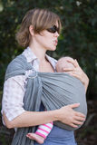 Mother holding sleeping baby. Held by baby carrier wrap Royalty Free Stock Images