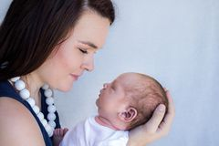 Mother holding sleeping newborn baby up to her face looking at him. Face to face smiling Royalty Free Stock Photography