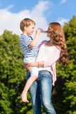 Mother holding son in arms kissing him Royalty Free Stock Photo