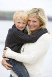 Mother holding son at beach smiling. At camera stock photo