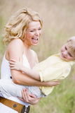 Mother holding son outdoors smiling Royalty Free Stock Photos